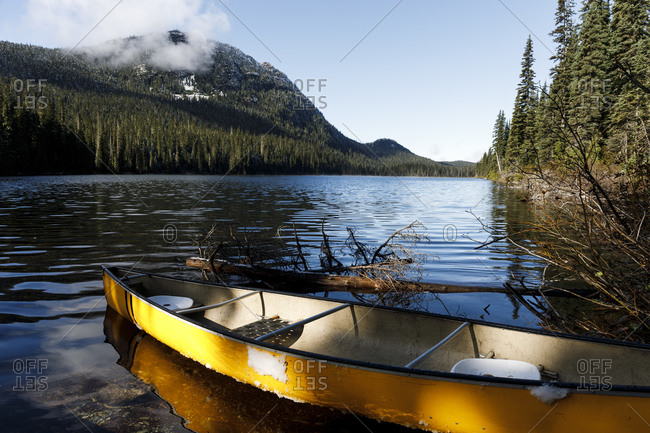 Yellow canoe pulled up on beach of calm alpine lake on an autumn day