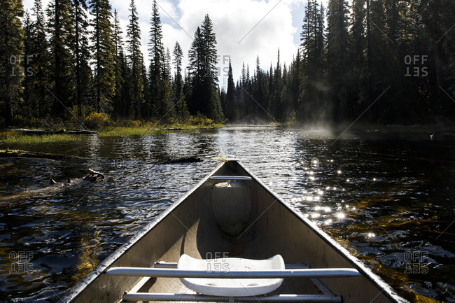 Bow of a canoe in the afternoon on a misty lake surrounded by forest