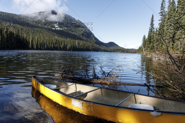 Yellow canoe floats on the shore of remote alpine lake on sunny day