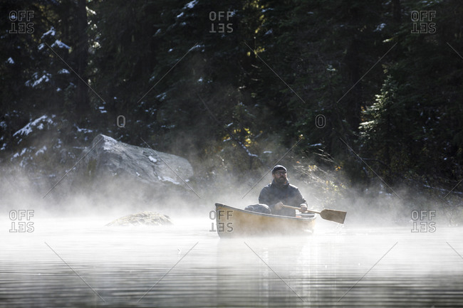Man holds a paddle in a canoe and takes in the outdoors on a foggy day