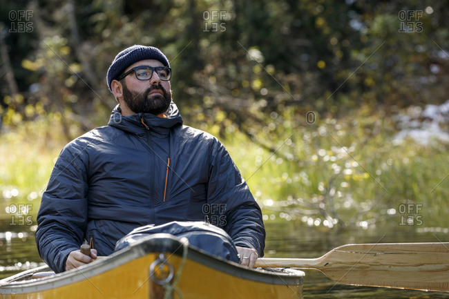 Sincere man sits in canoe on calm lake and takes in the outdoors