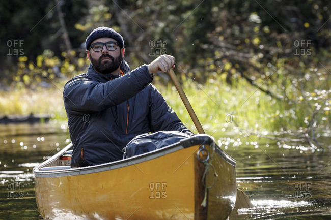 Sincere bearded man with hat and glasses paddles canoe on calm lake