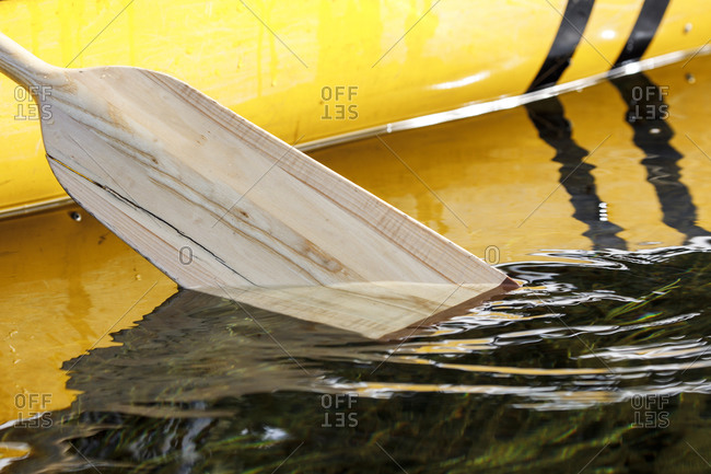 Close-up of canoe paddle dipping in tranquil remote lake