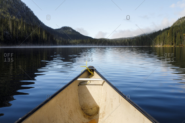 Bow of canoe on tranquil lake in canada surrounded by forest