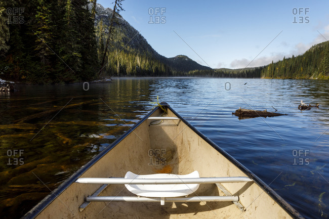 Bow of a canoe a secluded lake surrounded by forest, mountains and sky