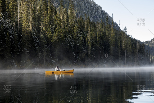 Bearded man paddles yellow canoe on calm misty lake by trees