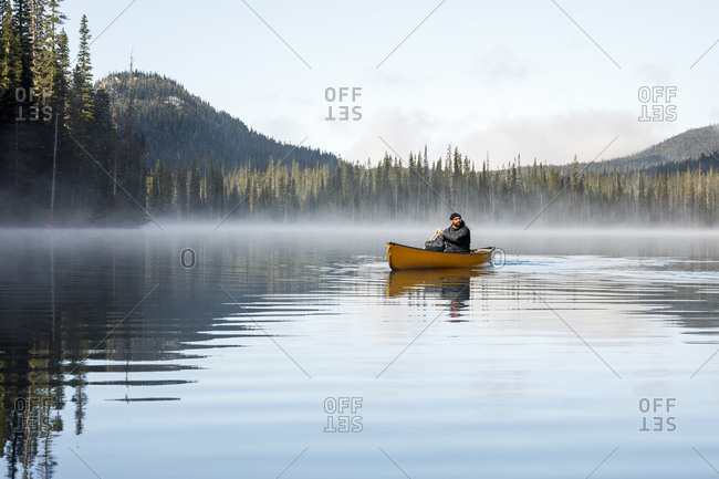Rugged man paddles canoe on misty calm lake by thick forest