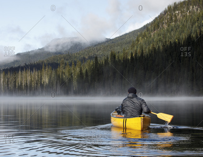 Back view of man paddling boat on calm misty lake in canada