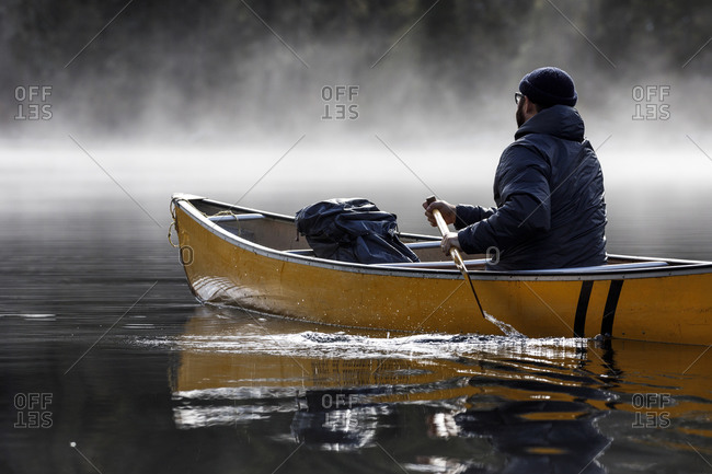 Bearded man paddles boat in lake during foggy weather