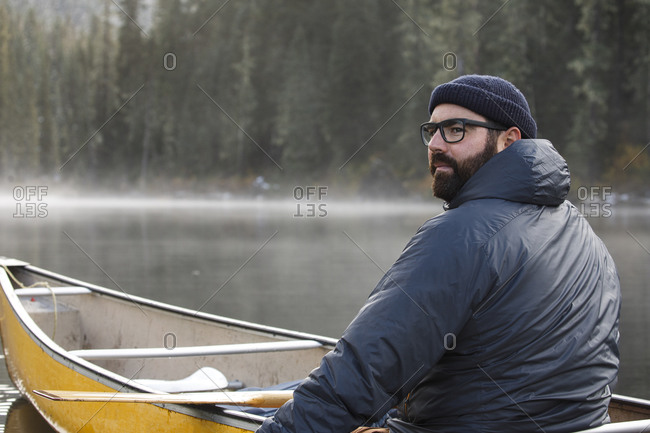 Portrait of sincere man canoeing on lake on a foggy, misty day