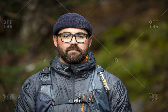 Portrait of an outdoor traveling bearded man with glasses and hat