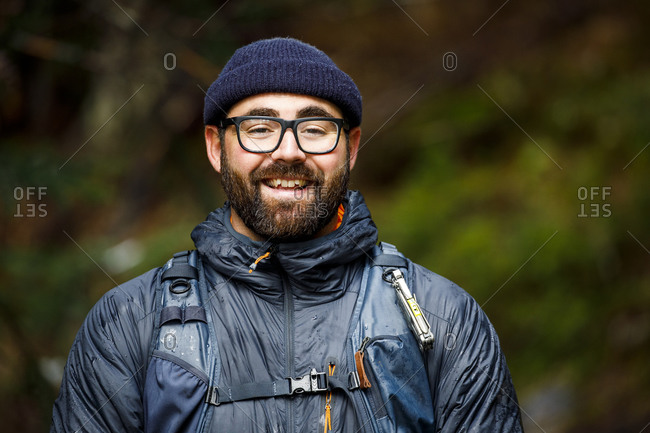 Portrait in nature of excited man in hat and glasses in outdoors