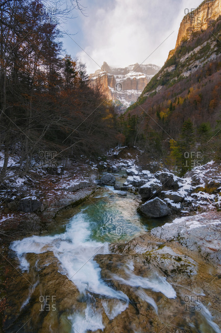 River through snow valley with waterfall, mountains and snowy trees