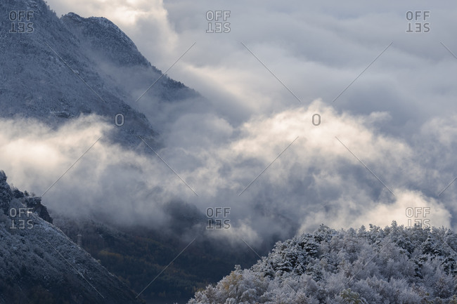 Clouds  between mountains in a snowy landscape at winter