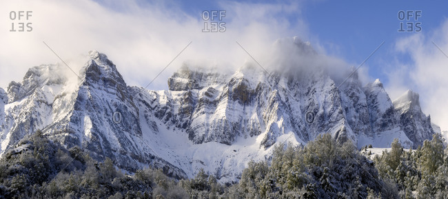 Clouds  between mountains in a panoramic snowy landscape at winter
