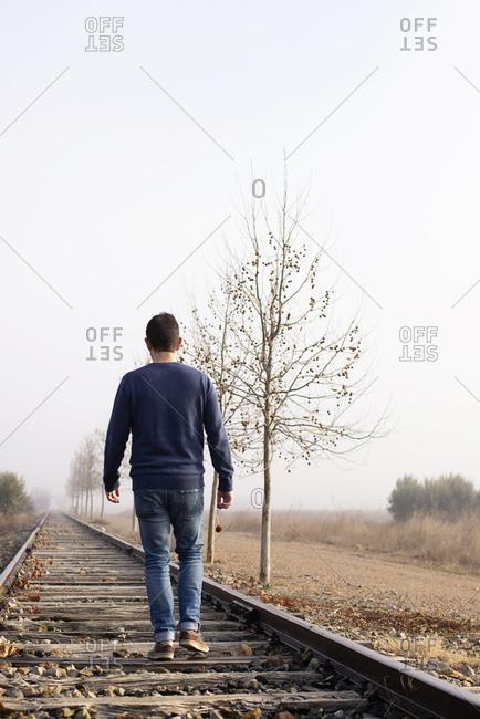 Rear view of a man walking along the railway tracks.