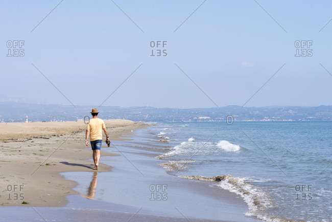 Rear view of man with hat, holding shoes walking barefoot on seashore