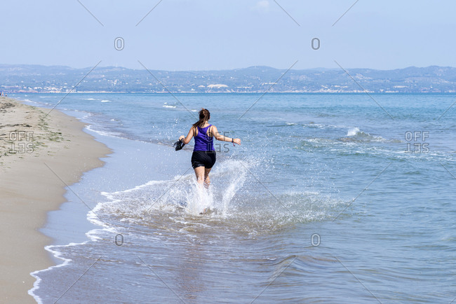 Back view of a woman in shorts running on seashore splashing water