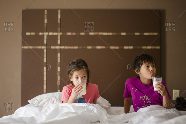 Two small children lay together in king size bed drinking cups of milk