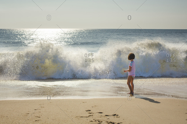 A small girl stands at edge of ocean watching wave break onto beach