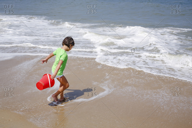 A little girl with a bucket plays in the tide at edge of sandy beach