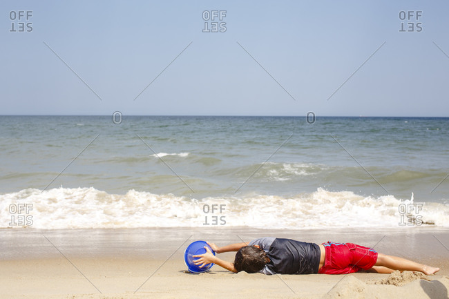 A boy lays on a beach with a blue bucket waiting for oncoming wave