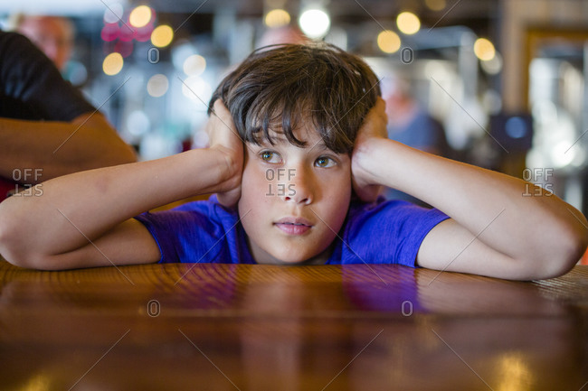 A boy with head in hands sits at restaurant table waiting patiently