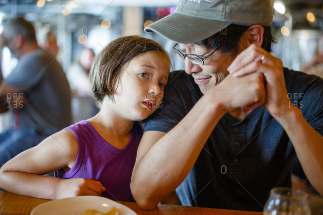 A father smiles down at child leaning on him in crowded restaurant