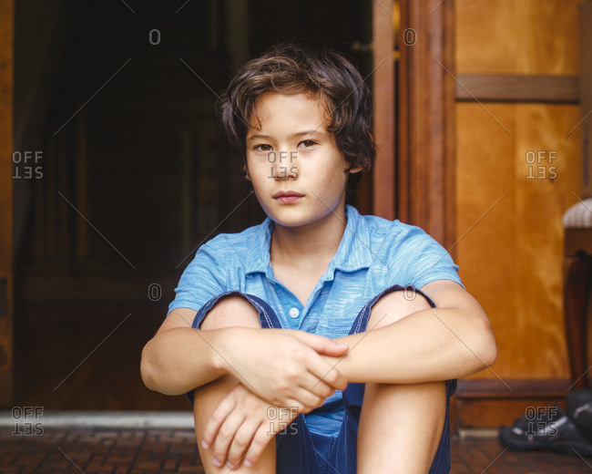 A boy with golden skin and serious expression sits in doorway of home