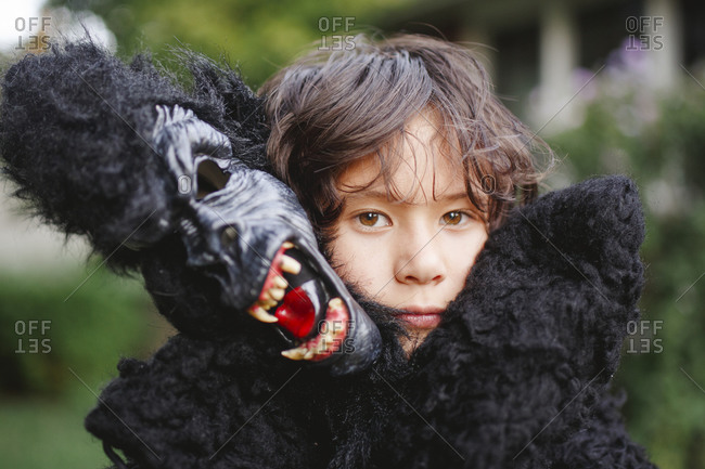 Close-up of beautiful boy wearing a gorilla costume outside