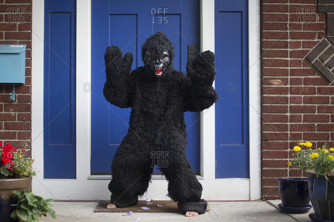 A boy wearing a gorilla suit and mask stands barefoot on front stoop