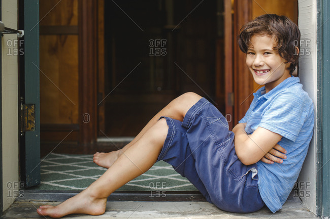 A boy with missing teeth sits smiling in a font entryway barefoot