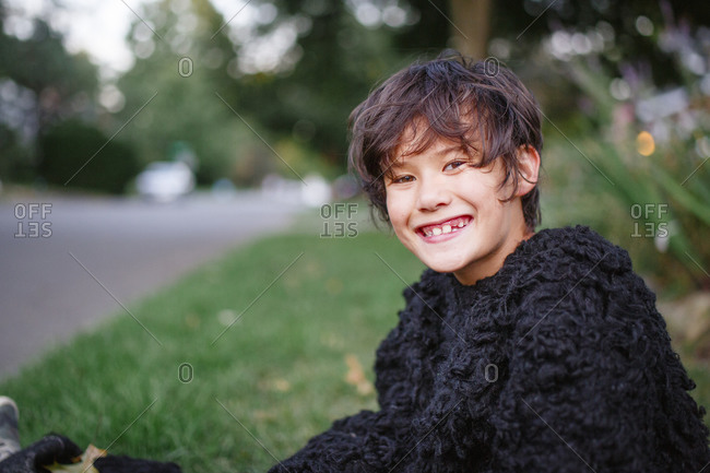 A happy boy in a gorilla suit smiles and sits in a grassy yard