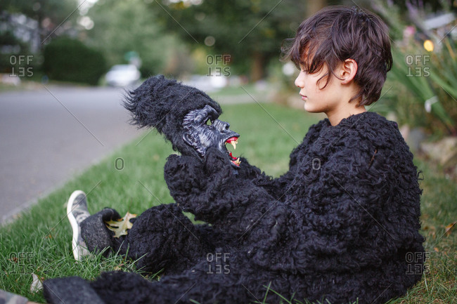 A boy sits in grass in gorilla suit looking at scary gorilla mask