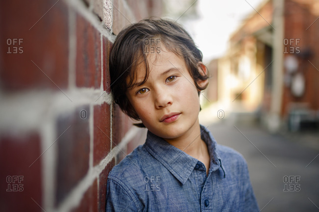 A beautiful serious boy leans against wall in sunlit brick alley