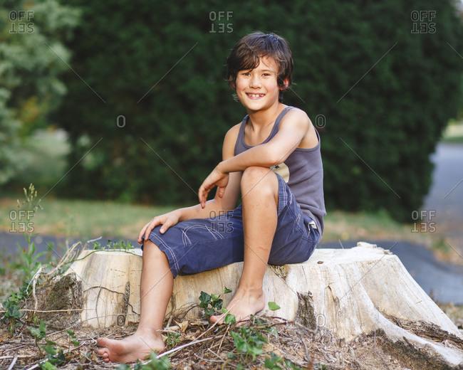 Portrait of happy barefoot boy with golden skin sitting on tree stump