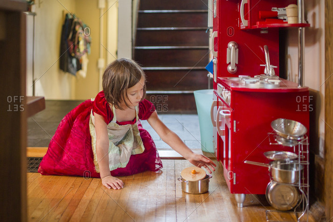 Little girl wearing apron and party dress plays with toy kitchen