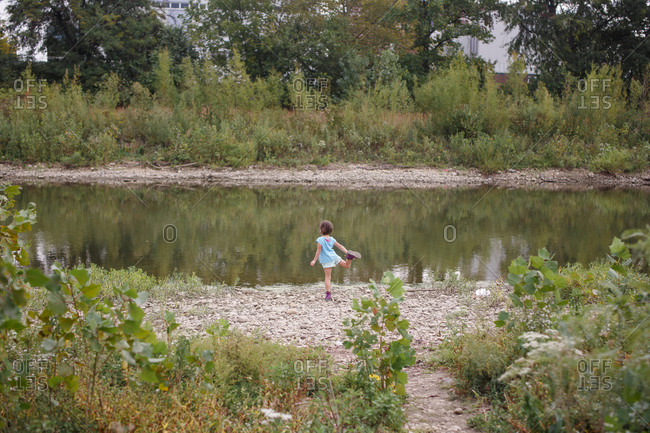 Distant view of girl standing on shore of river balancing on one leg