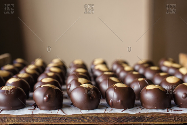 Rows of neatly lined up chocolate candies spread out on a wooden board