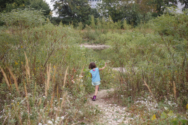 A little girl walks through tall grass and wildflowers on stone path