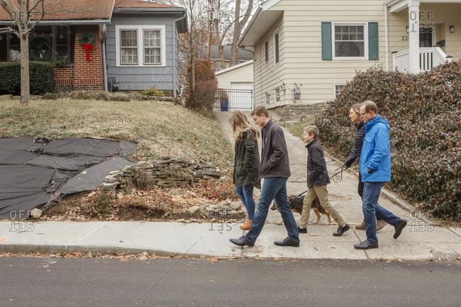 A family walk together with dog through suburban neighborhood