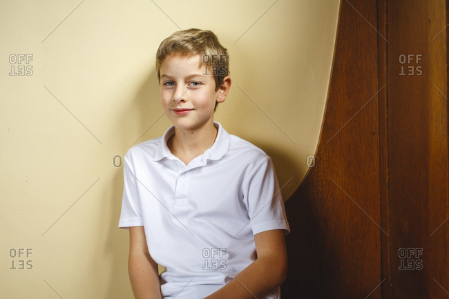 A young boy sits on wooden bench leaning against wall with direct gaze