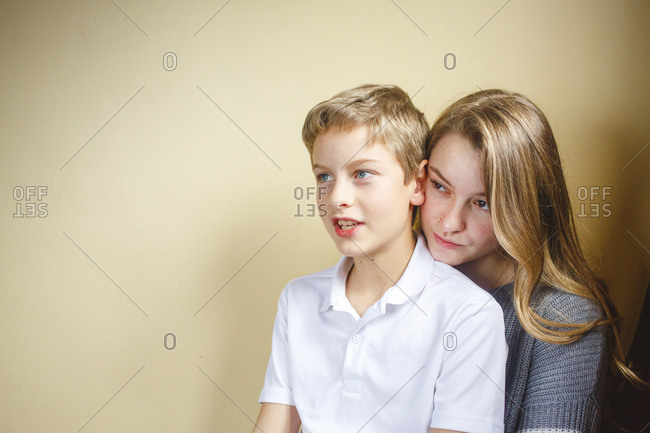 A young boy sits on his sisters lap smiling in soft window light