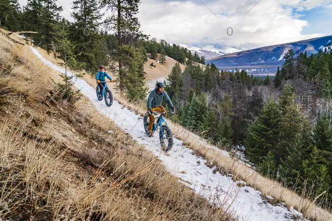 Couple fat biking winter trails in jasper national park