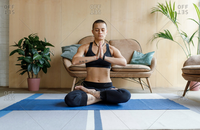 Young short haired woman meditating in lotus yoga pose at home