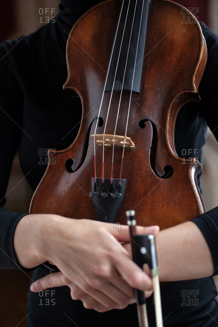 Female musician hands hugging violin near body in black dress