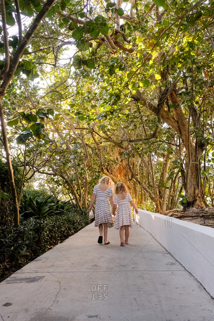 Two girls walking on path holding hands through trees