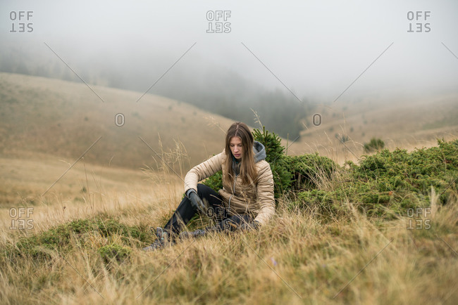 Blonde girl sitting down in the grass