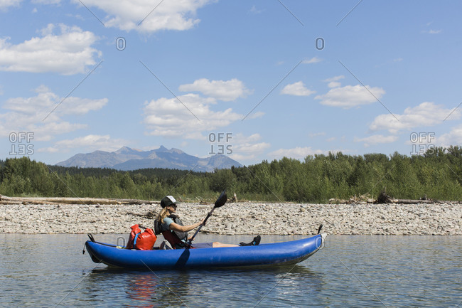 A young woman floats on a north fork of the flathead river.