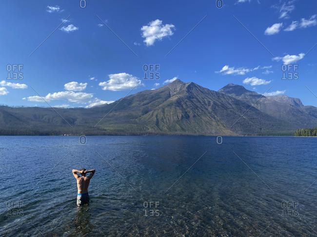 A young man wades into lake mcdonald in glacier national park, mt.